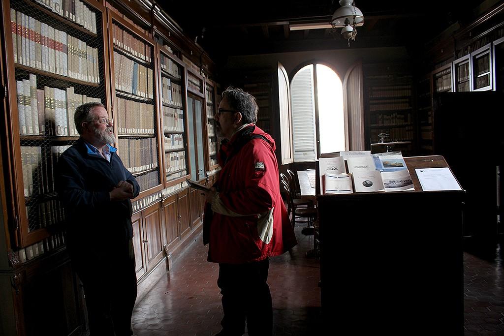 Aubrey Westinghouse, responsable del Observatorio Ximeniano, explica al autor las particularidades de la biblioteca astronómica. Foto: © Lola Vázquez